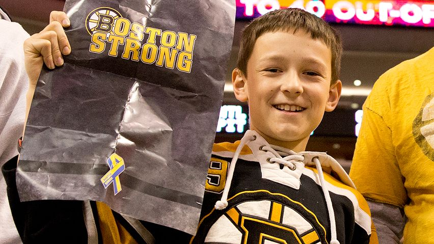Cole Fagan told CBC the game was both happy and sad. Here, he holds one of the thousand Boston Strong posters the Bruins organization handed out before the game.