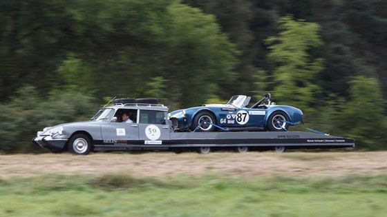 Jochen Mass driving a modified Citroen DS transporter with an AC Cobra strapped on the back