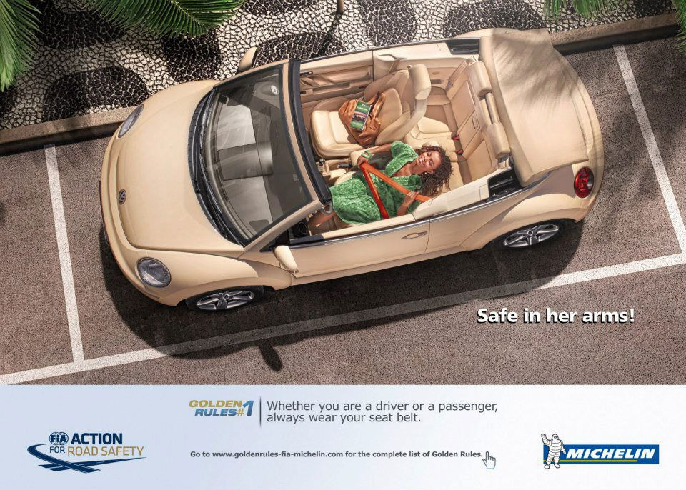 Safe in her arms! Golden Rules #1: Whether you are a driver or a passenger, always wear your seat belt. Go to www.goltlenrules-fia-michelin.com for the complete list. FIA Action For Road Safety. Michelin.