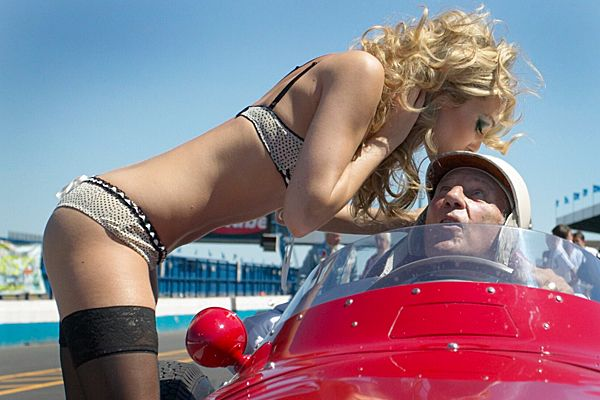 Woman in lingerie kissing Stirling Moss' helmet. Even at 80 years of age Sir Stirling Moss doesn't seem to have any trouble getting beautiful women to throw themselves at him. Here he is at Donington Park about to take a Maserati 250F out for a drive. Credits to the image go to http://blog.neillwatson.com/opinions/sir-stirling-moss-the-blonde-and-the-mystery-of-the-stolen-image