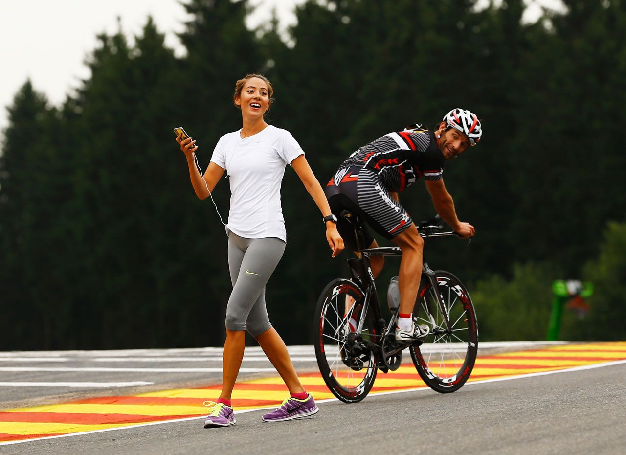 Mark Webber on a bicycle watching Jessica Michibata walking at the Circuit de Spa-Francorchamps