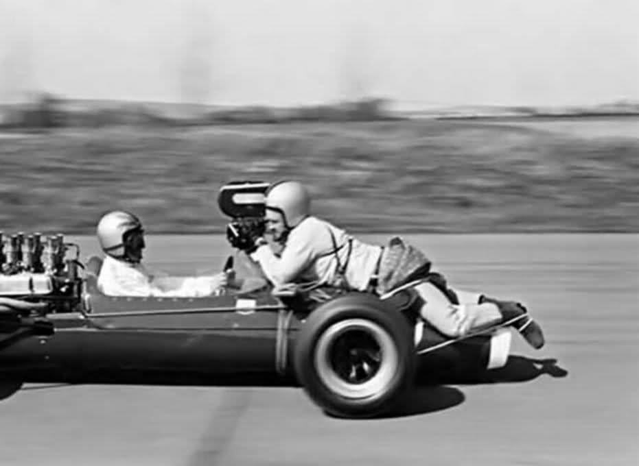 Cameraman onboard filming a race car sitted at the nose of the car