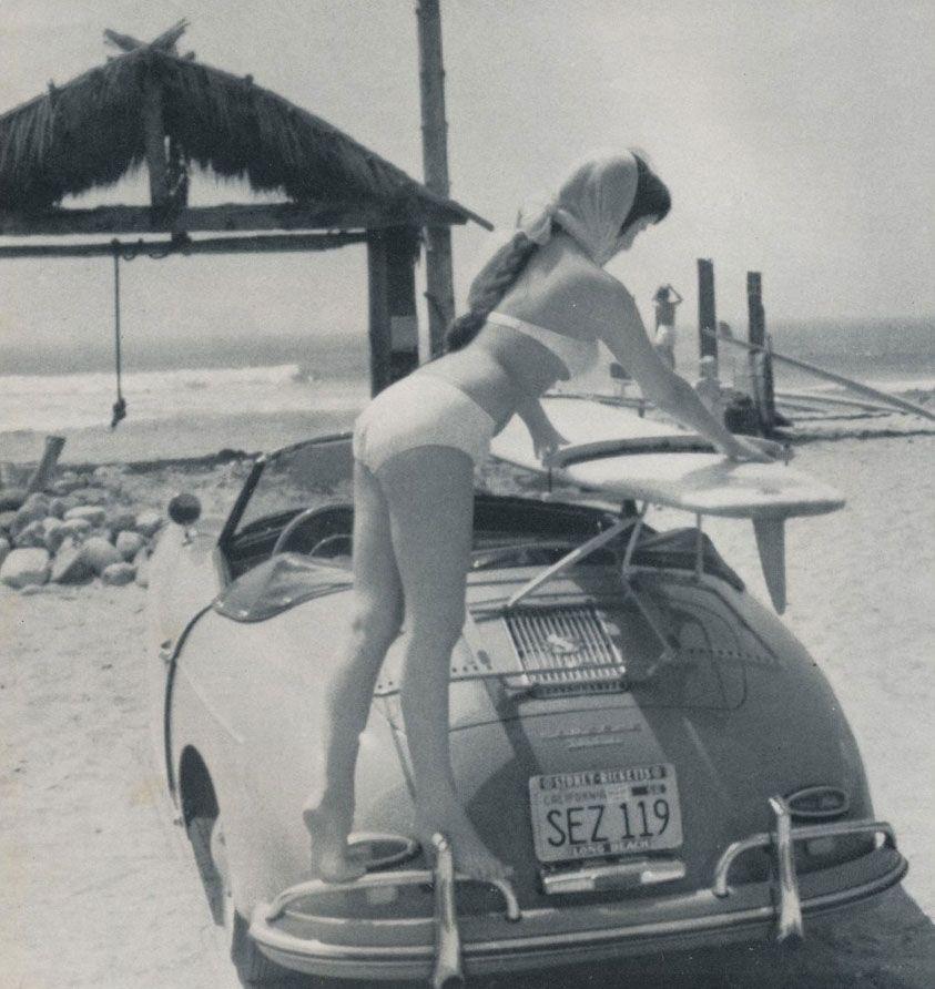 Woman removing a surf board from a Porsche Speedster