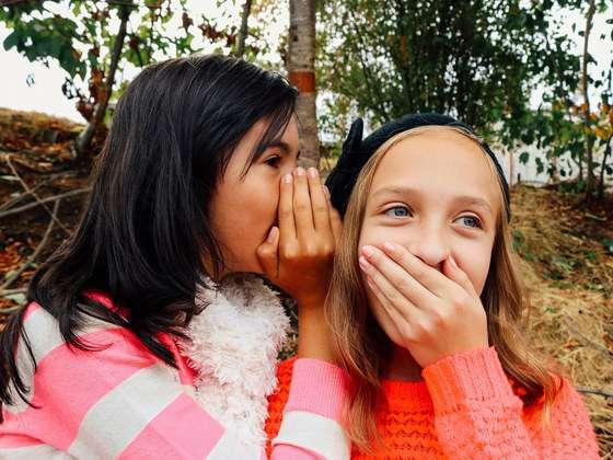 Two children whispering