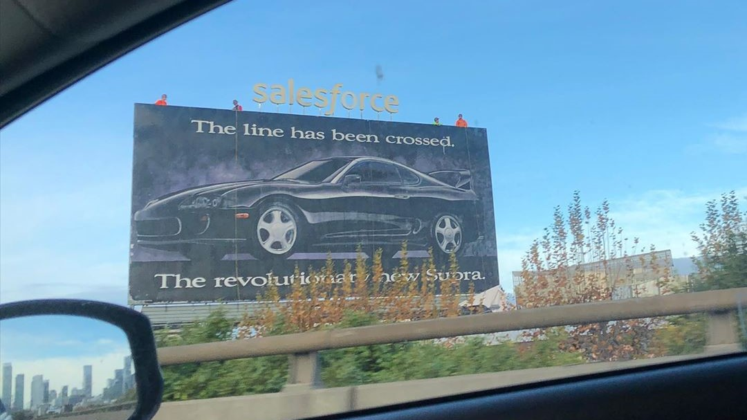 """The line has been crossed. The revolutionary new Supra"" A 1993 Toyota Supra A80 hand-painted in an outdoor at San Francisco, California, United States, by Clear Channel Communications, a group of iHeartMedia"