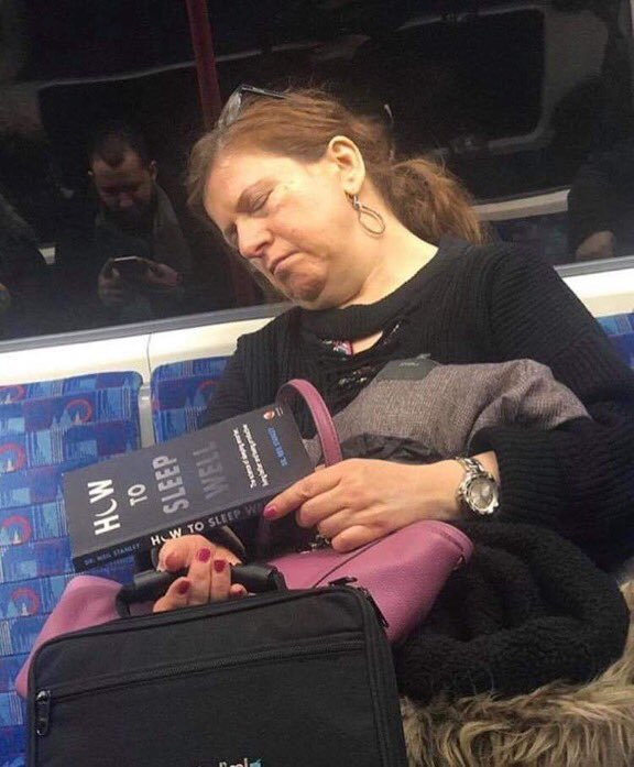 Woman sleeping inside a train with a book How To Sleep Well in the left hand